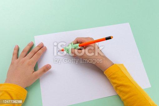 470761441 istock photo Three point fingers pen holding practice, preschooler boy writing homework, handwriting correction tool, writing training 1247736288
