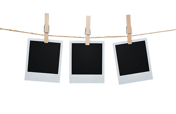 three polaroid pictures hanging on a clothesline with pins - polaroid stockfoto's en -beelden