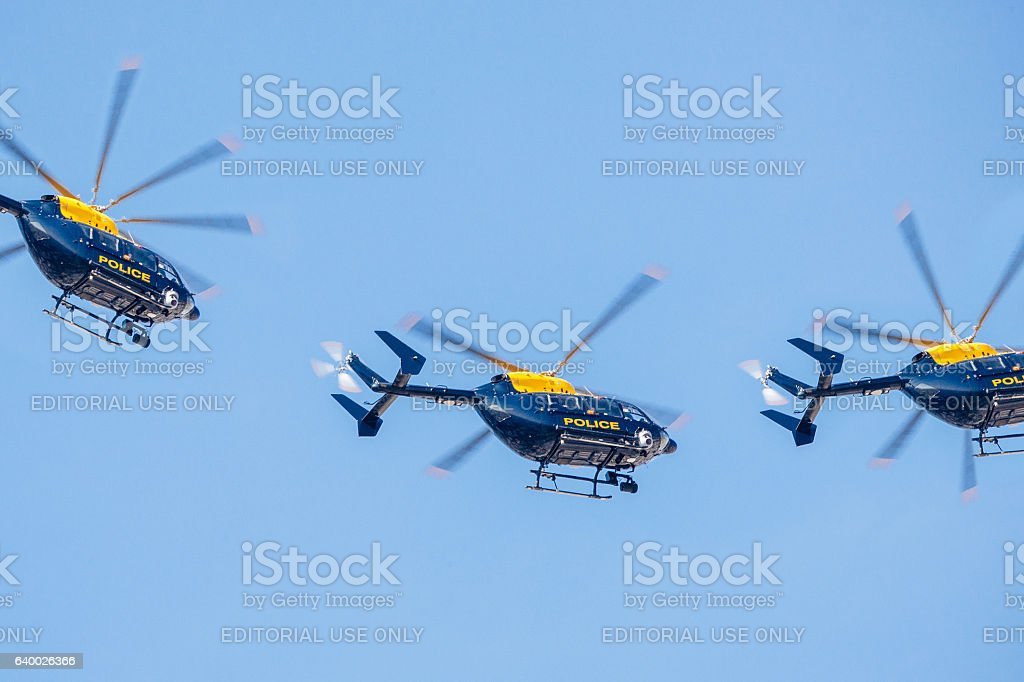 Three police helicopter flying against a clear blue sky stock photo