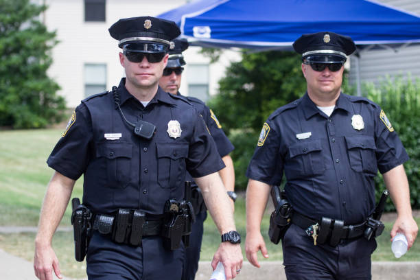 Three Police Officers Walking at the Roots and Heritage Festival Lexington, Kentucky, United States - September 9, 2016:  Three police officers walking during Lexington's 2016 Roots & Heritage Festival.  The Roots & Heritage Festival is a popular event that celebrates African American culture and features musical and dance performances, a marketplace, and a parade.  For over 25 years on the weekend following Labor Day, the Roots and Heritage Festival has been a pinnacle of regional diversity providing education and entertainment to people of all ages. police uniform stock pictures, royalty-free photos & images