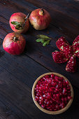 three pomegranate with bowl on real wooden table wonderful colors