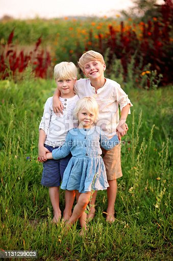 Three precious little blonde caucasian children are smiling and holding hands outside in the garden on a summer day.