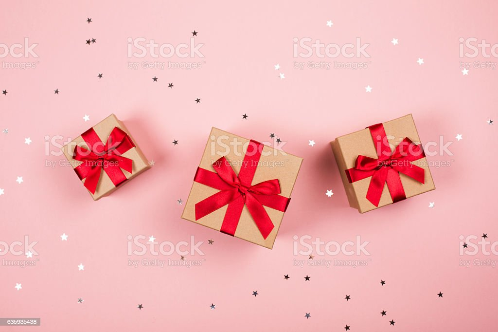Three presents with red bow on pink Three presents with red bow on pink background with tittle sparkles. Flat lay style. Above Stock Photo