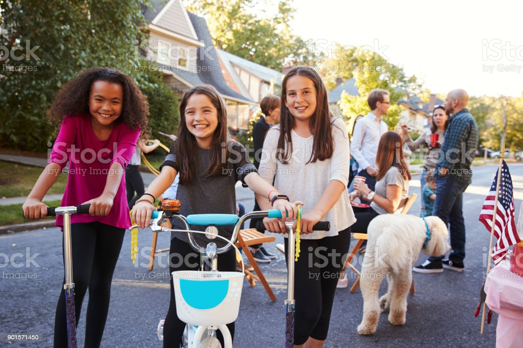 Three pre-teen girls on scooters and a bike at a block party stock photo