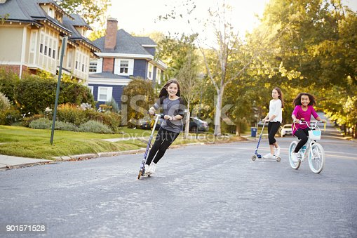 Three pre-teen girls playing in street on scooters and bike