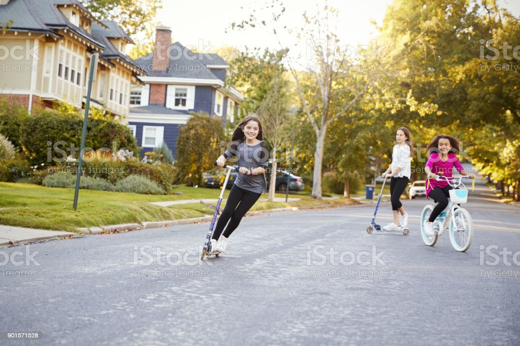 Three pre-teen girls playing in street on scooters and bike stock photo