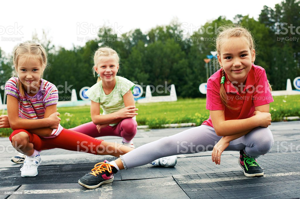 three pre-teen girls starting to run on track stock photo
