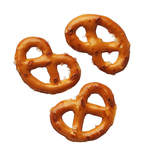 three pretzels isolated on white background, close-up - 椒鹽蝴蝶圈 個照片及圖片檔