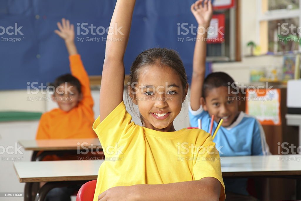 Three primary school children hands raised in class royalty-free stock photo