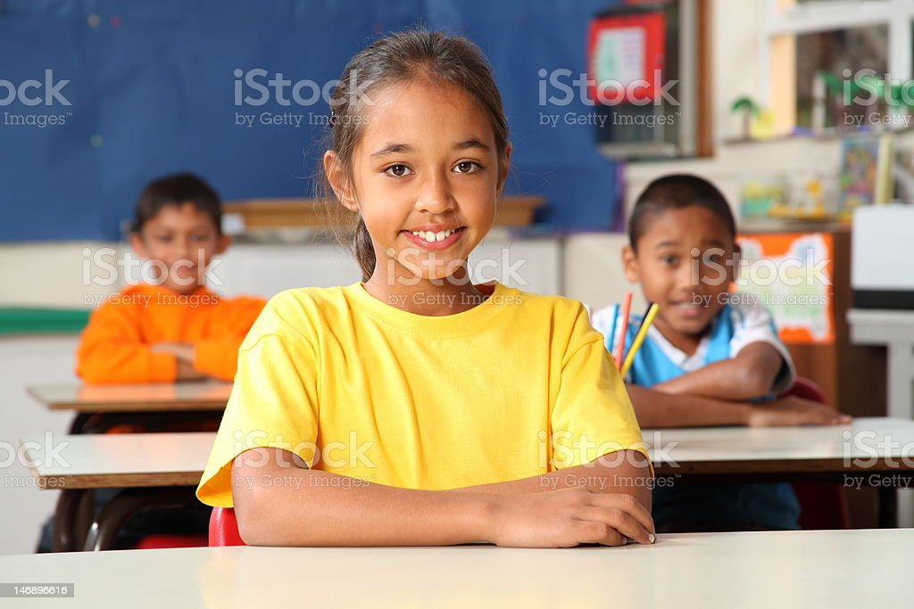 Three primary school children sitting to desks in their class royalty-free stock photo
