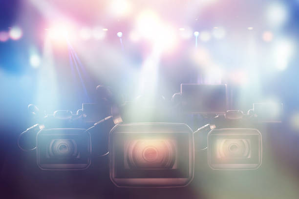 three professional video camcorder in studio with blurred lights on stage background stock photo