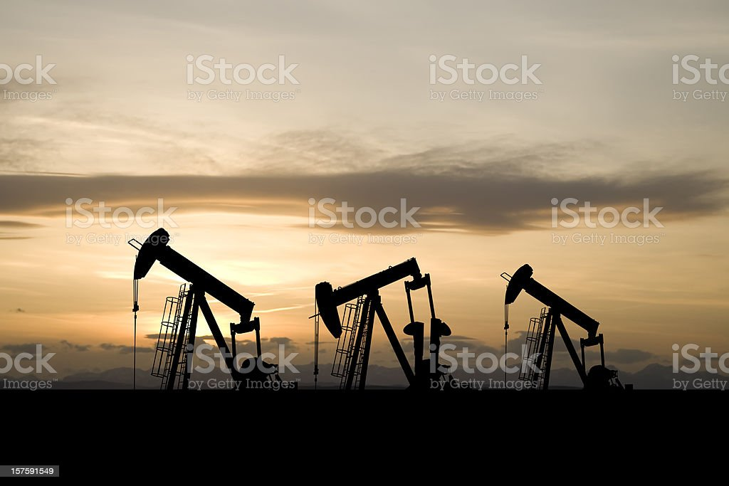 Three Pumpjacks and a Yellow Sky stock photo