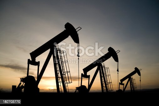 A royalty free image from the oil industry of three pumpjacks on a prairie at sunrise.