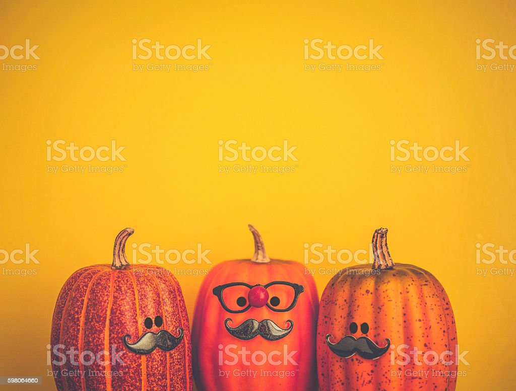 Three pumpkin characters wearing mustaches for Halloween stock photo