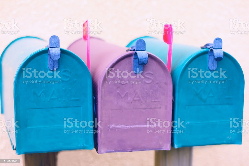 Three Purple and Blue Rural Mailboxes with Red Flags Up stock photo