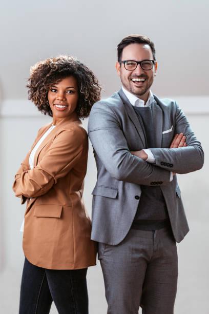 Three quarter length business portrait of cheerful multi ethnic couple stock photo