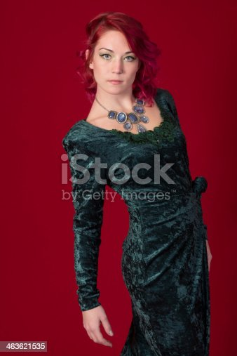 Vertical studio shot on red of young woman in green dress with silver and blue necklace.