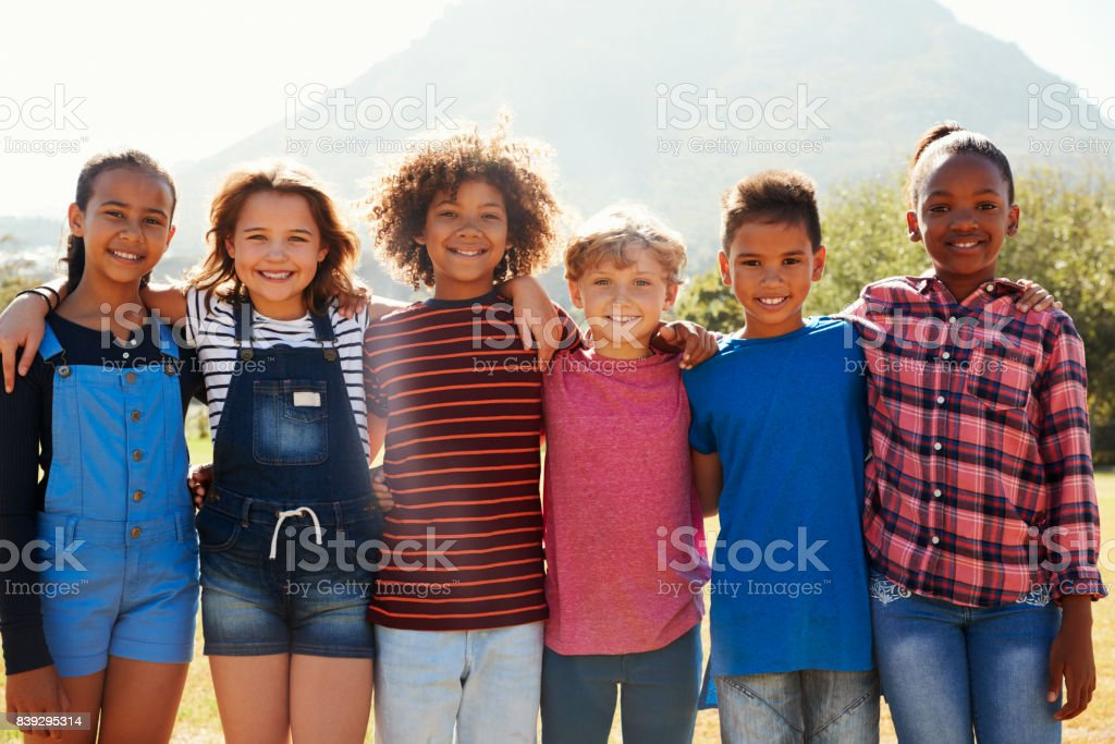 Three quarter length portrait of pre-teen friends in a park stock photo