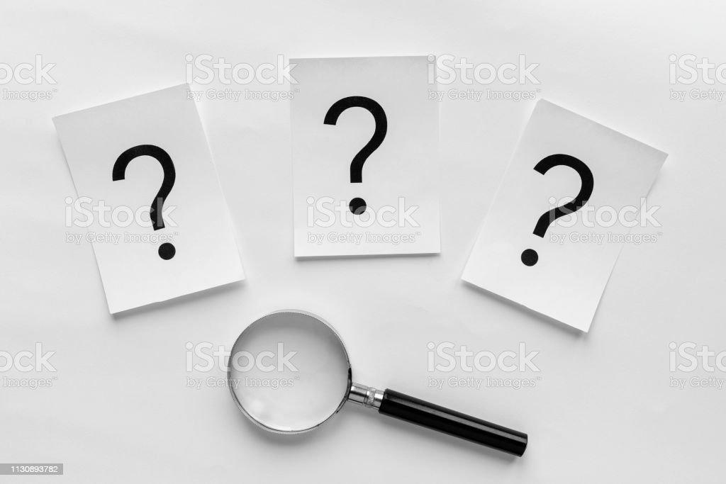 Drei Fragezeichen mit einer Lupe – Foto