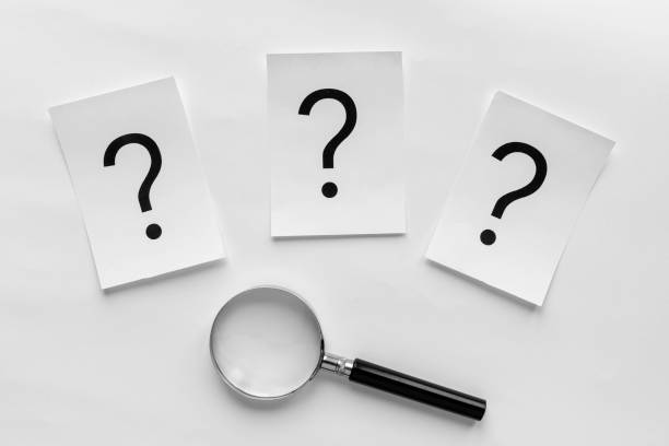Three question marks with a magnifying glass stock photo