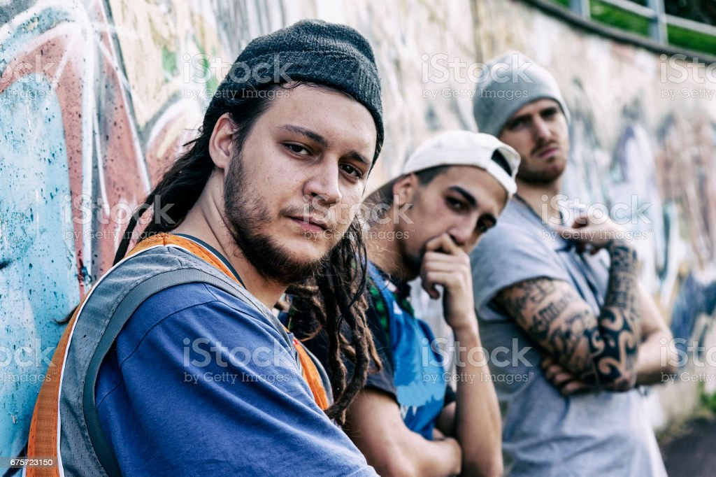 three rap singers in a subway with graffiti in the background stock photo