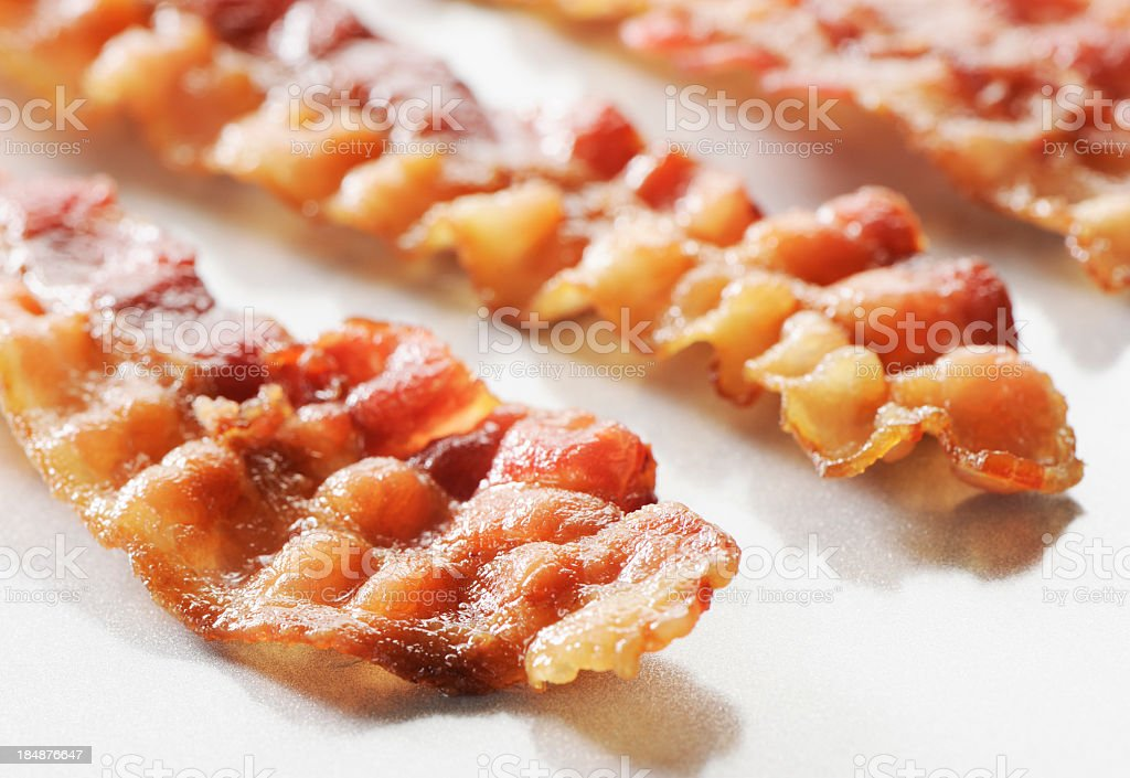 Three rashers of crispy sliced bacon on a white background stock photo