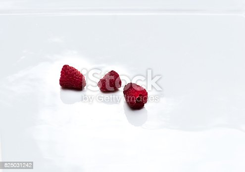 istock Three raspberries on white with reflection 825031242