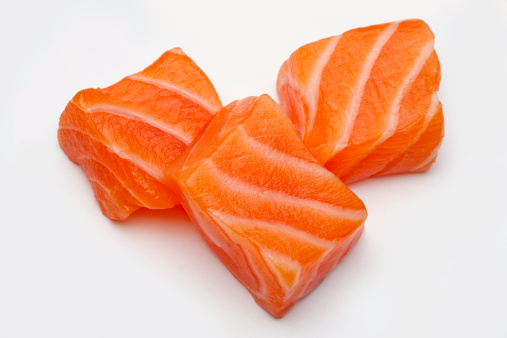 Three raw salmon fish meat cut up into cubes or chunks photographed in the studio on a white surface.