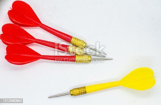 919544754 istock photo Three Red and one Yellow darts in the Opposite direction. Concept the odd one to hit the target. 1212580952