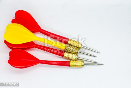 919544754 istock photo Three Red and one Yellow darts in the same direction. Concept the odd one to hit the target. 1212580935