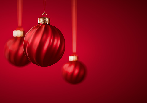 Three red Christmas balls. Twisted striped Christmas ornaments hanging against burgundy red background. Christmas decoration, festive atmosphere concept. Selective focus, copy space.