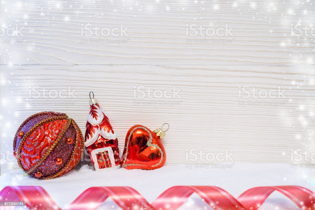 Three red Christmas toys and red twisted tape are lying on snow on light wooden background. stock photo