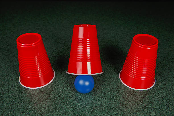 Three Red Cups and a Blue Ball Shell Game – three red cups and a blue ball on a green table arranged like the shell game.  Copy space in upper half of the frame fades to black.  This photo could be applicable to many concepts including – gaming, decision making, risk, reward, opportunity, solution strategy, and many others. shell game stock pictures, royalty-free photos & images