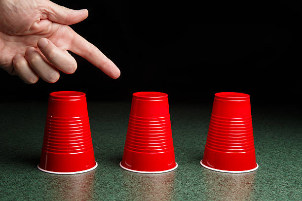 Three Red Cups and a Pointing Hand Shell Game - three red cups on a green table arranged like the shell game with hand pointing to the center cup.  Copy space in the upper half of the frame.  This photo could be applicable to many concepts including – gaming, decision making, risk, reward, opportunity, help, and many more. shell game stock pictures, royalty-free photos & images