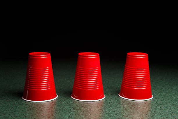 Three Red Cups - Shell Game Shell Game - three red cups on a green table arranged like the shell game.  There is copy space in the upper half of the frame which fades to black.  This studio close-up could be applicable to many concepts including – gaming, decision making, risk, reward, opportunity, luck and many others. shell game stock pictures, royalty-free photos & images