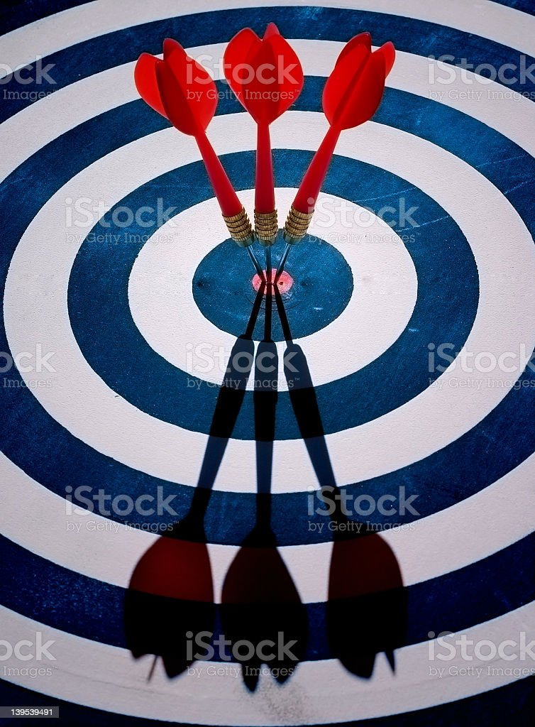 Three red darts in the center of a blue bull's eye stock photo