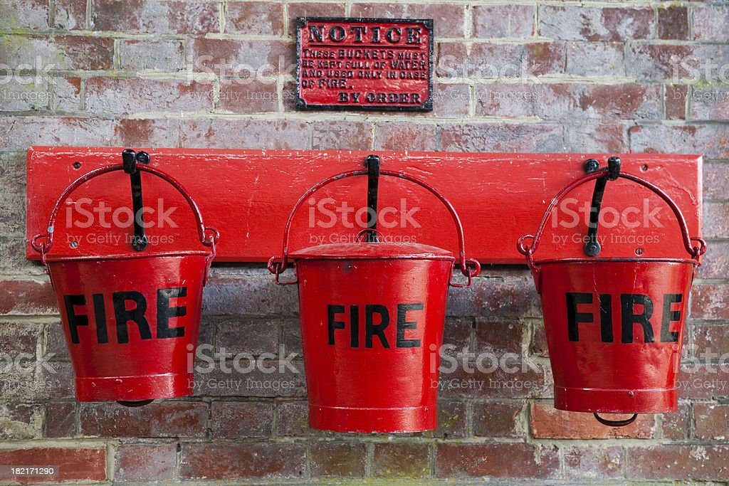 Three red fire buckets on wall royalty-free stock photo