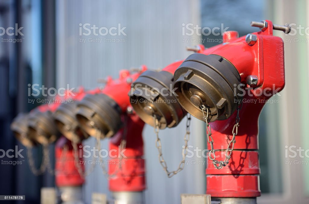 Three red fire hydrant pipes stock photo