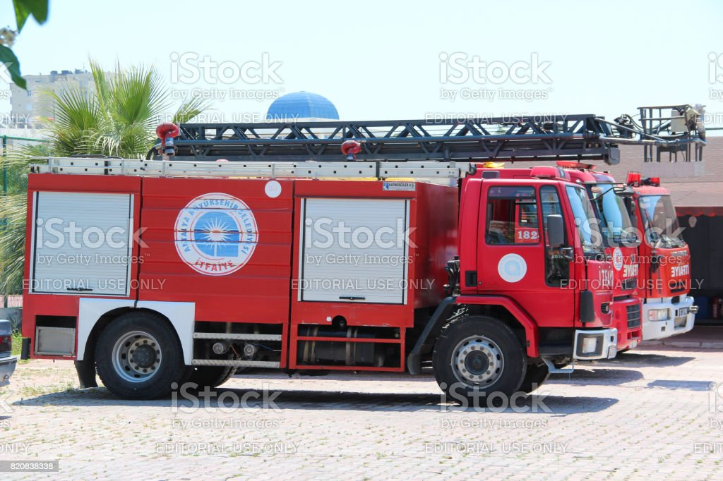 Three red firetruck with rescue ladder standing on the street of the city near firehouse stock photo