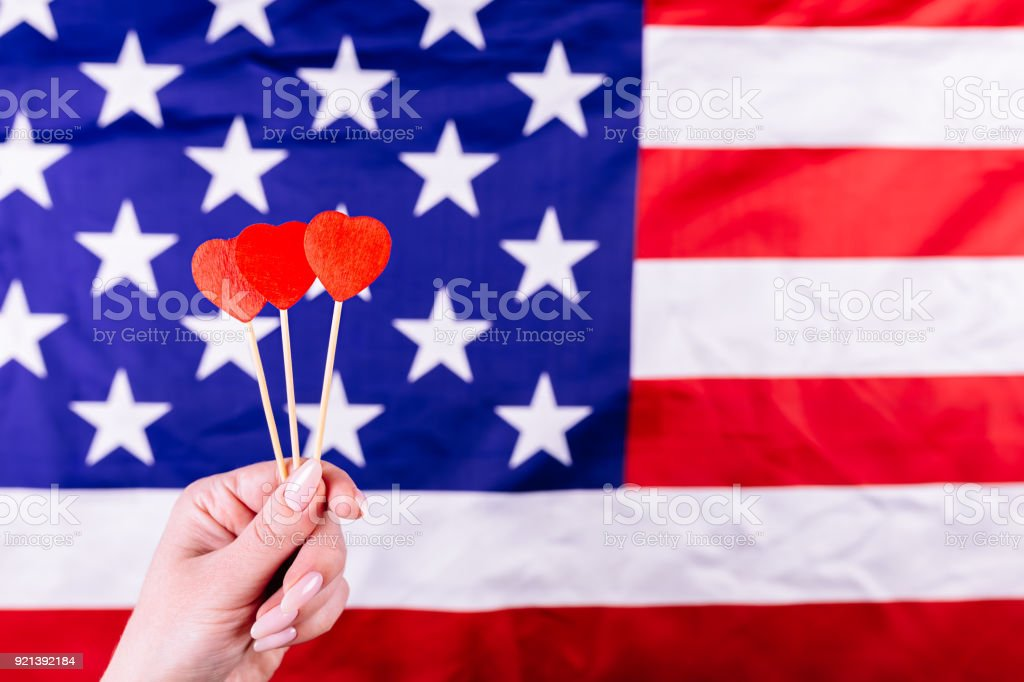 Three red hearts shape on stick in front of american flag. Visual concept of preparation for Independence Day. Fourth of July patriotic consept stock photo