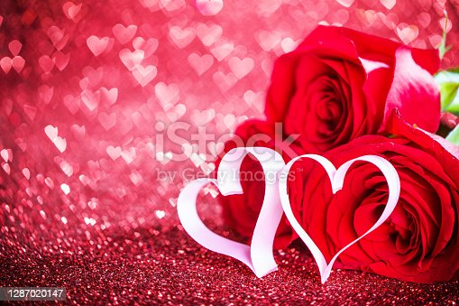 Three red roses and ribbon hearts and over hearts bokeh glittering background