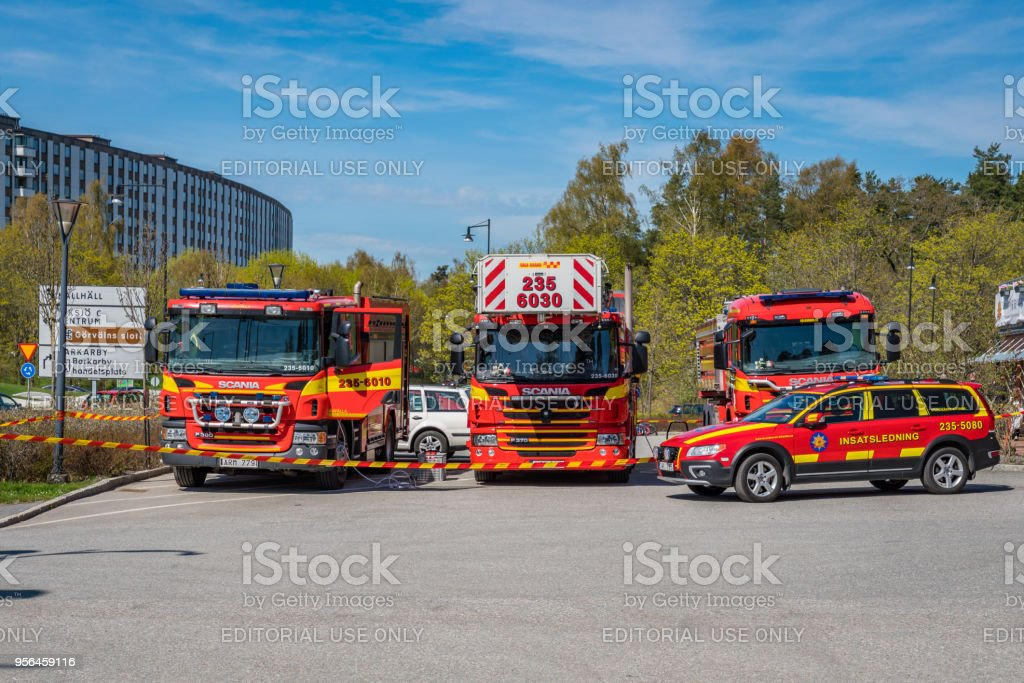 Three red Swedish fire-engines and a car parked outdoors. royalty-free stock photo