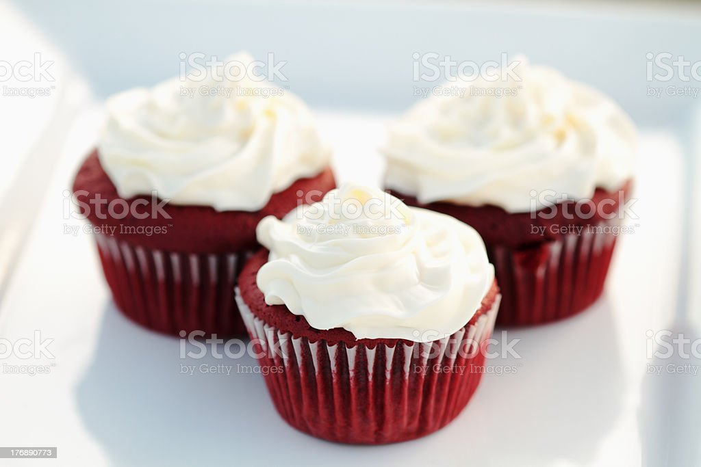 Three red velvet cupcakes on a white plate stock photo