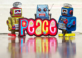 three retro robot toys holding a bright and colorful cloth peace sighn