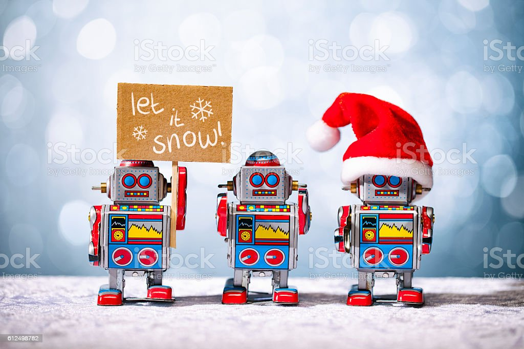 Three retro robots posing for Christmas. Let it Snow. Santa. stock photo