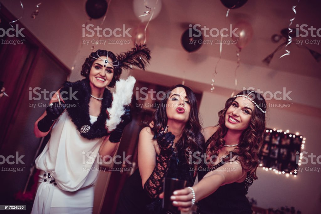 three retro style fashion females posing at new years eve theme party royalty free stock
