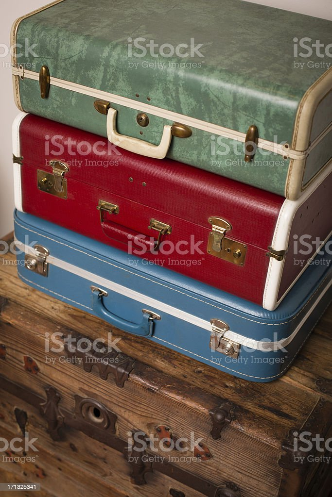 Three Retro Suitcases Stacked on Wood Trunk stock photo