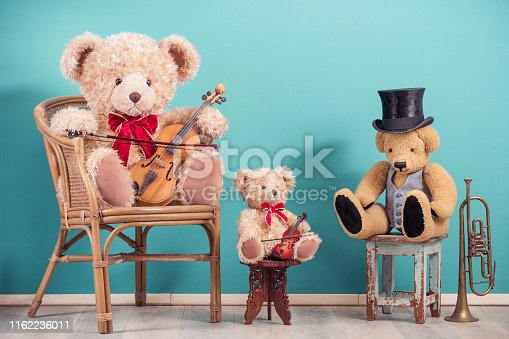 istock Three retro Teddy Bear toys with fiddles, cylinder hat sitting on wooden chairs, brass trumpet front aquamarine wall background. Music school lesson concept. Vintage nostalgia style filtered photo 1162236011