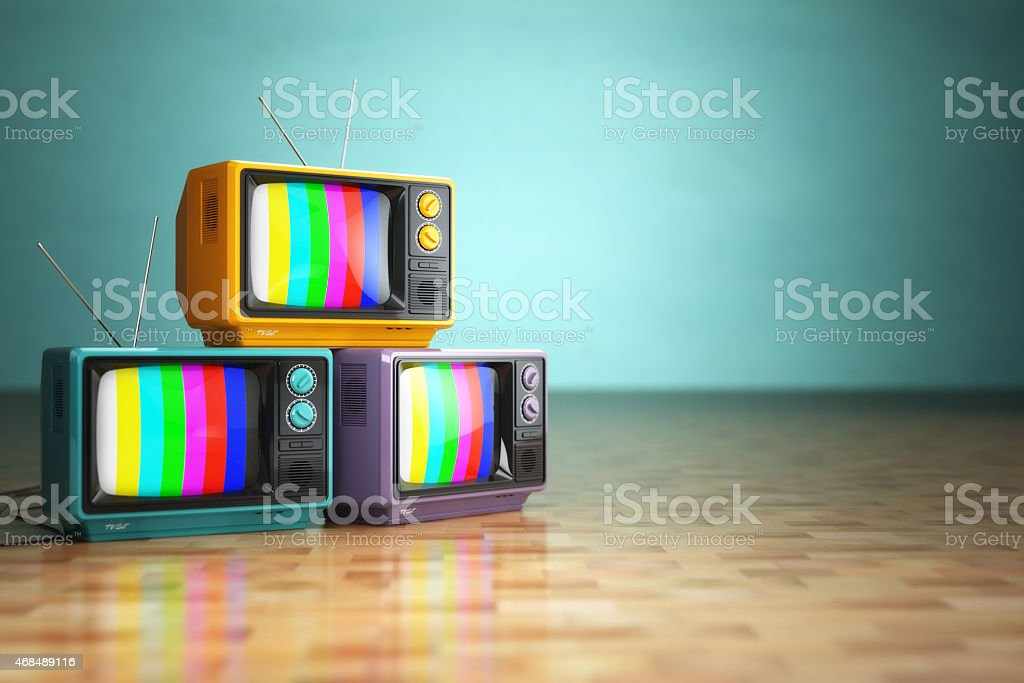 Three retro televisions stacked on a parquet wood floor stock photo