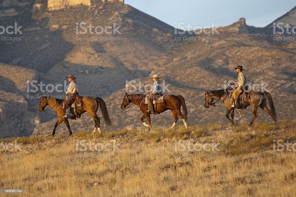 Three riders walk horses toward Wyoming sunset stock photo